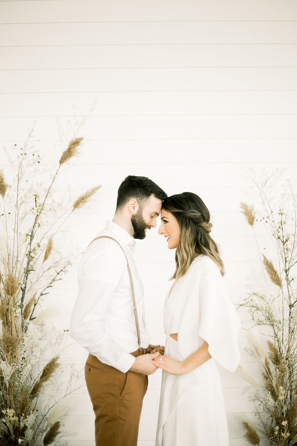 Modern bride and groom holding hands against shiplap wall at Walker Homestead with minimalist pampas and dried grass arch