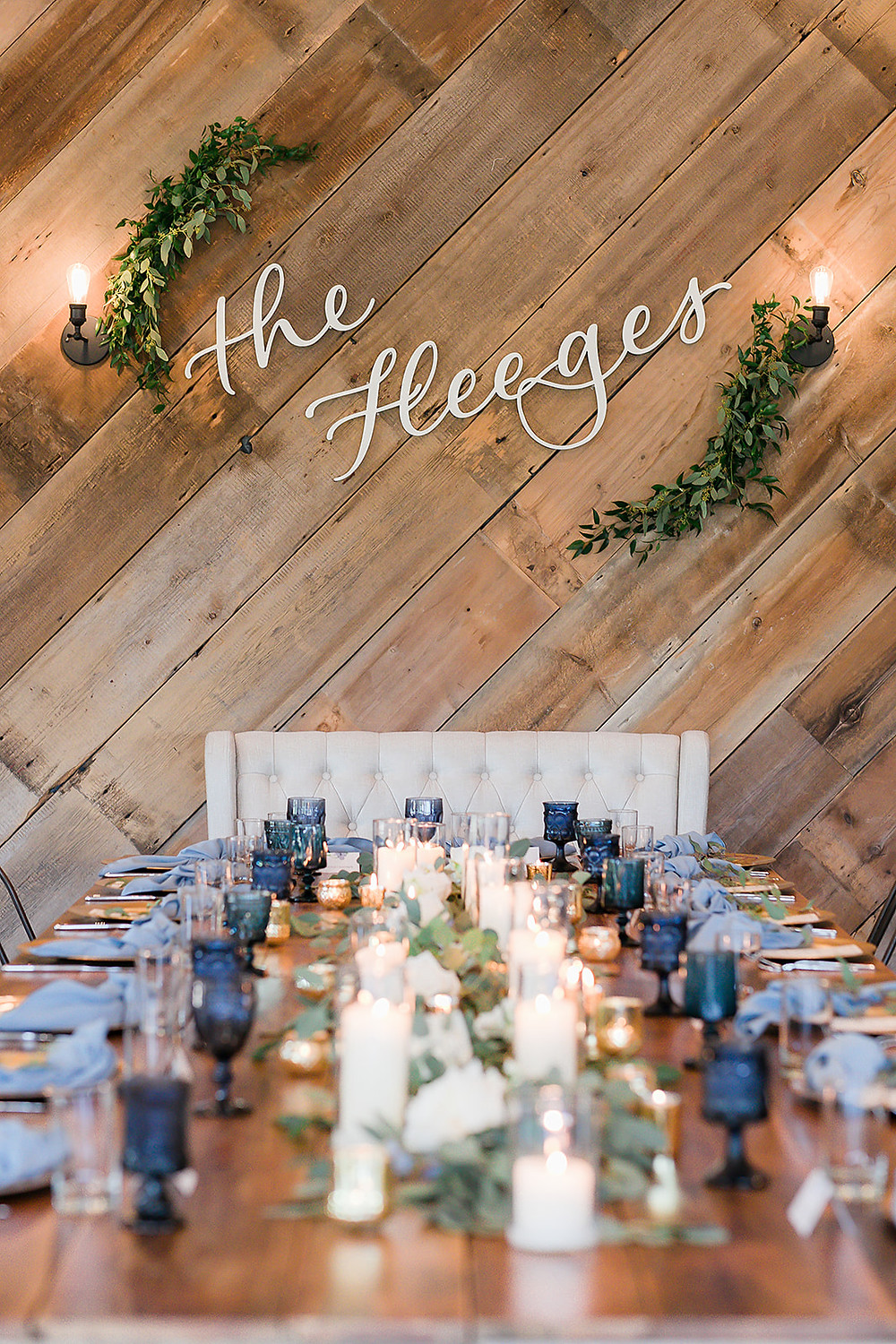Head table with eucalyptus greenery runner garland, roses, candles, and blue goblets