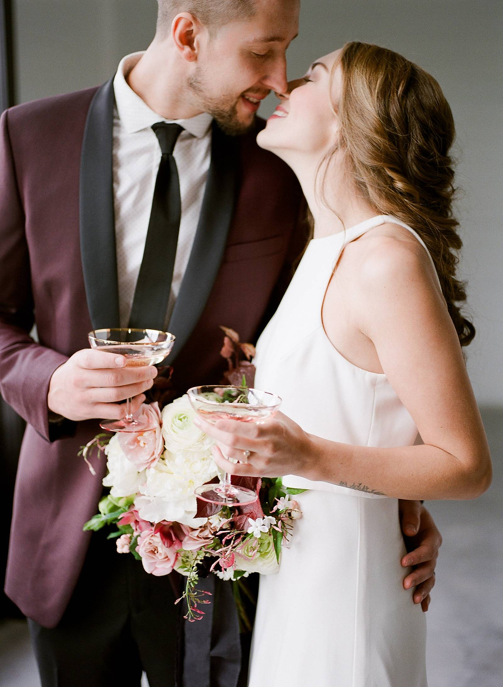 Bride and groom kissing with toasting glasses and bridal bouquet