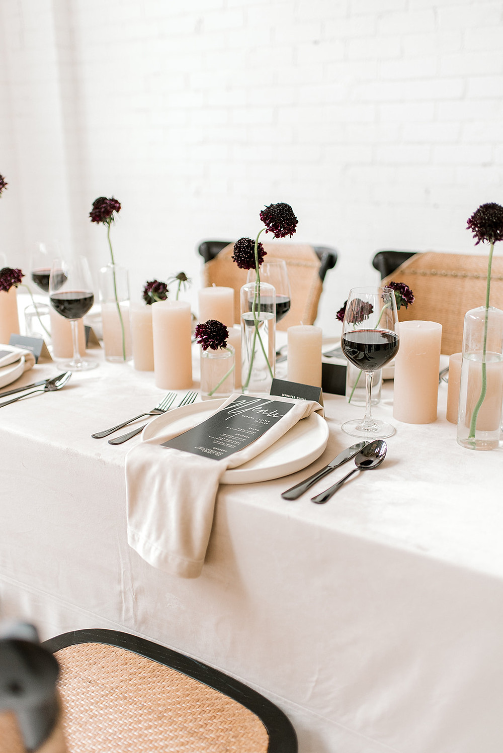 neutral minimalist wedding table with budvases of black scabiosa and beige pillar candles