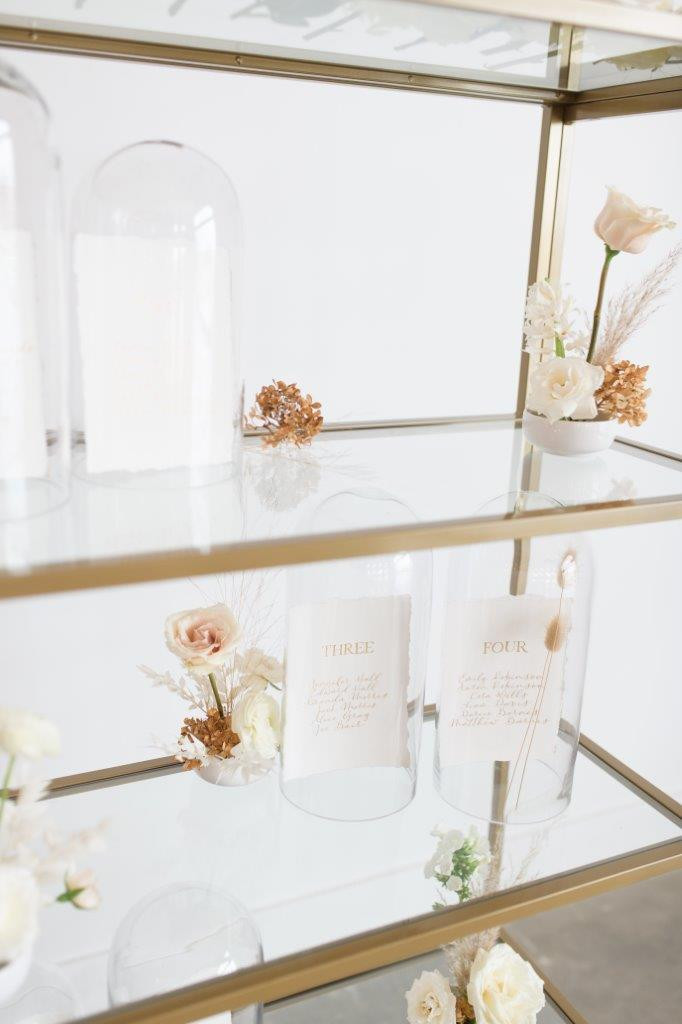 Minimalist wedding seating chart on gold shelves and calligraphy paper inside glass cloche dome with flowers by Studio Bloom