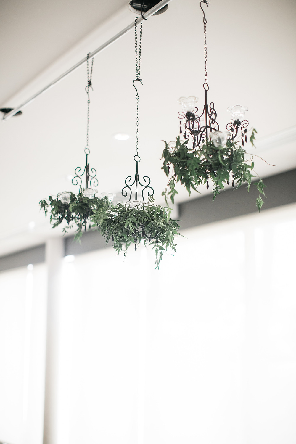 Petite wedding reception chandeliers with greenery foliage decoration hanging at eastbank venue