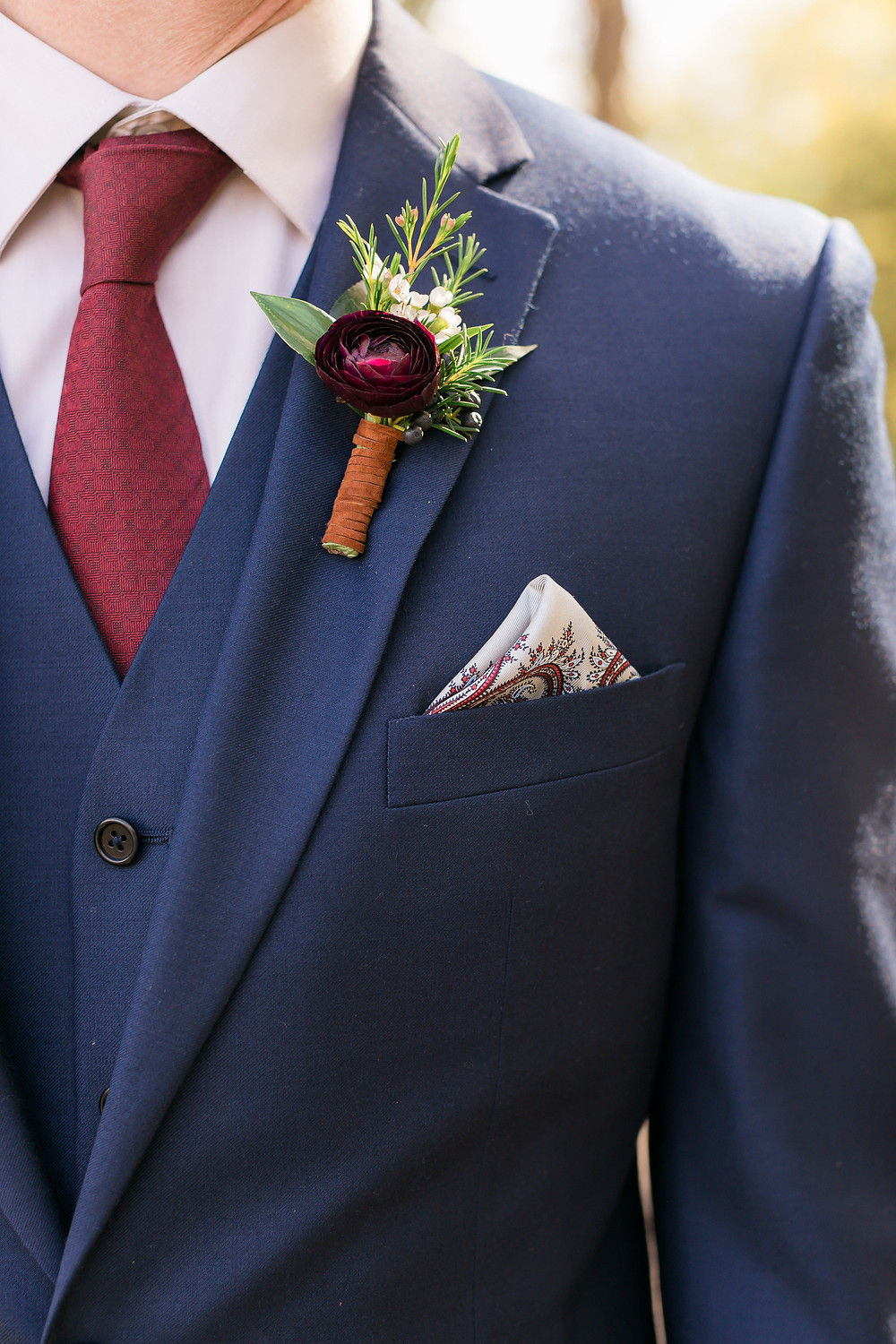 groom with burgundy ranunculus boutonniere and navy suit