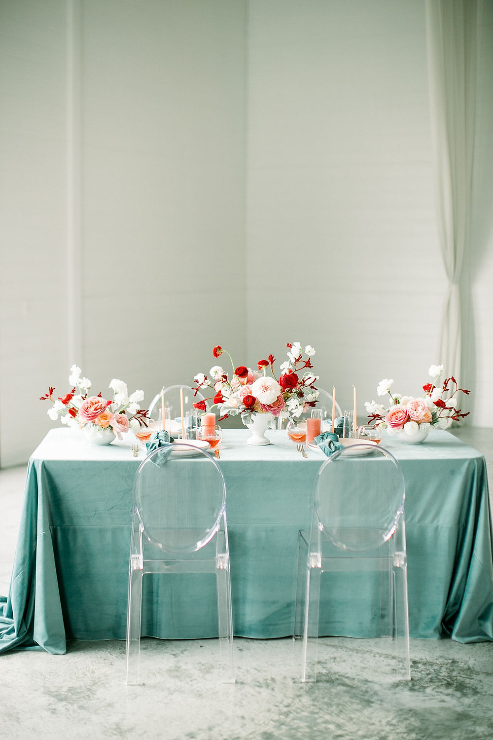 Red, and teal wedding tablescape with velvet linens, candles, ghost chairs, and floral centerpieces by studio bloom iowa