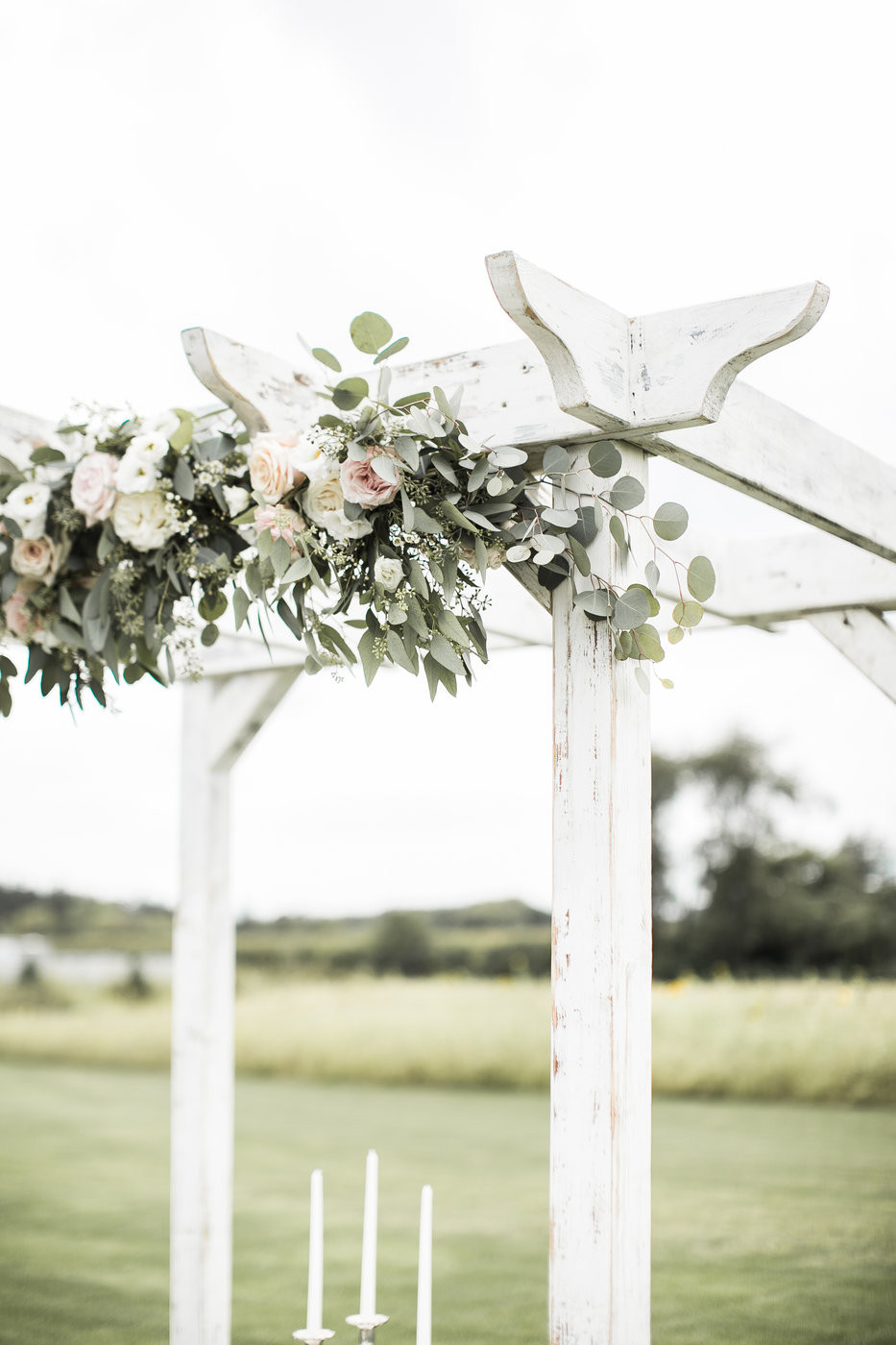 blush rose and eucalyptus garland by studio bloom iowa florist on white wood arbor for outdoor wedding ceremony at ashton hill