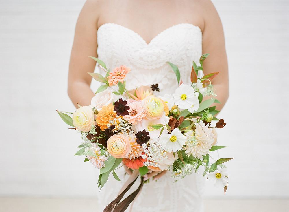 Bride holding earthy boho bridal bouquet by wedding florist studio bloom iowa with peach dahlias cosmos ranunculus and zinnias