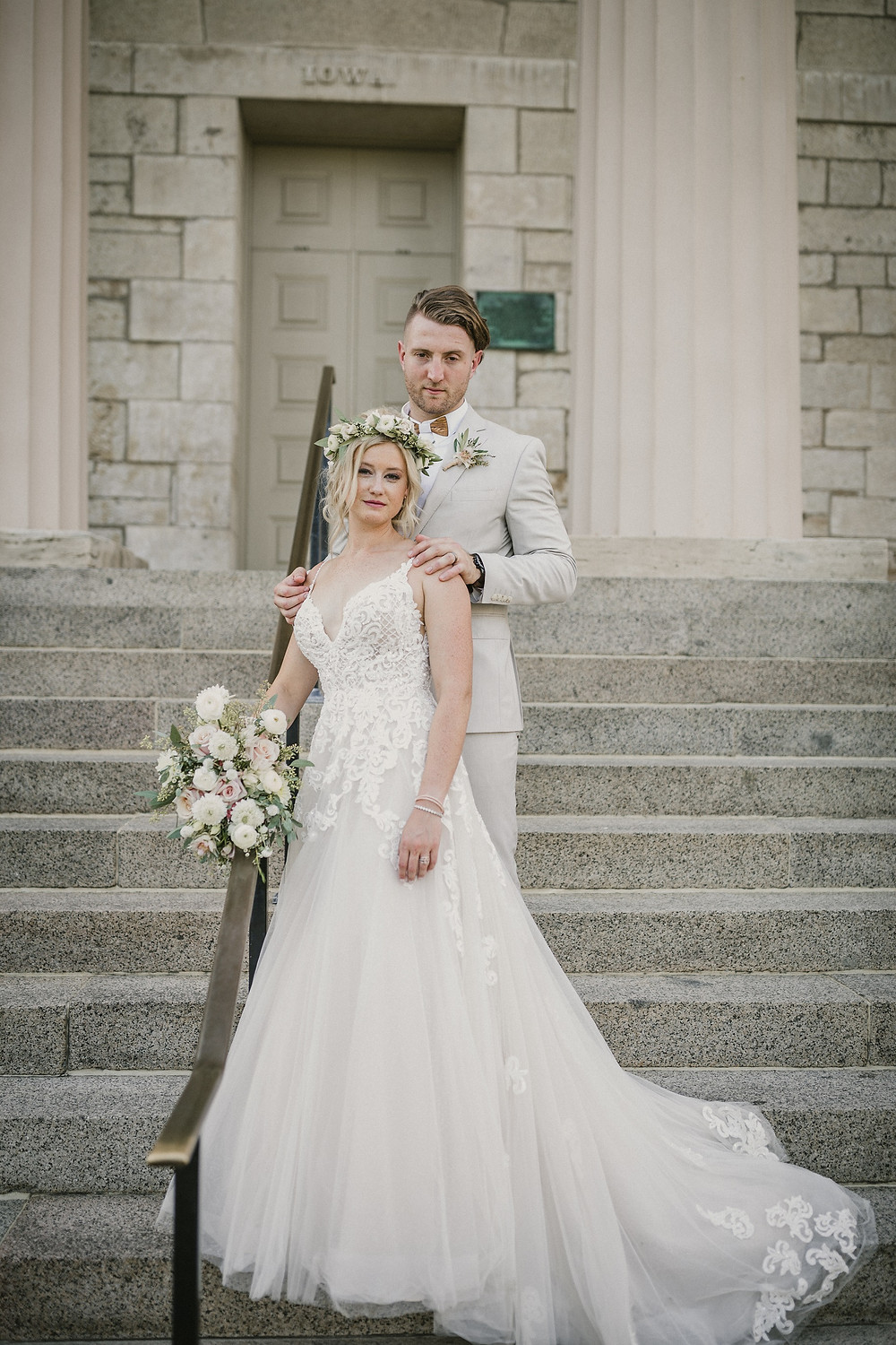 bride and groom posing on old capitol museum stairs at the university of Iowa in with bridal bouquet by studio bloom iowa