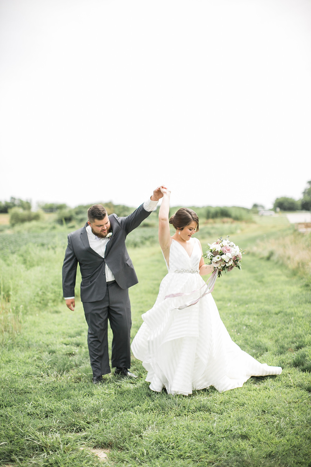 bride and groom dancing in a grass field with flower bouquet and striped dress