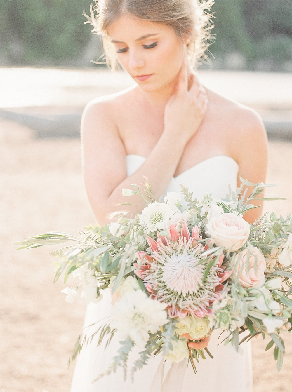 Studio bloom iowa wedding floral designer created a bridal bouquet of protea, roses, scabiosa, and olive for a beach wedding