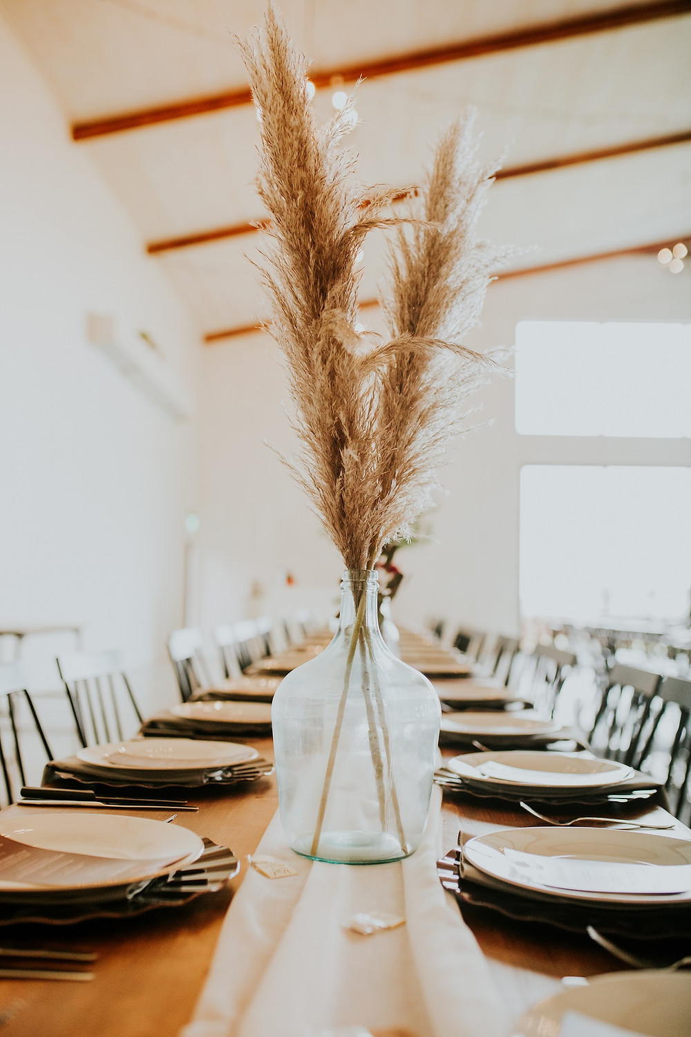 pampas grass in demijohn jug vase for a wedding centerpiece