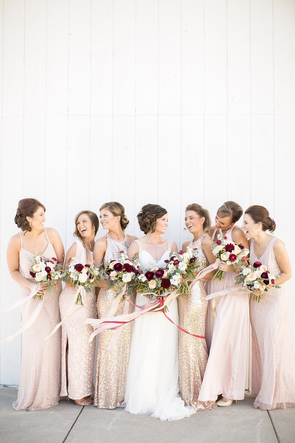bridesmaids in blush sequin dresses and bride with burgundy and blush bouquets by studio bloom iowa in front of white barn