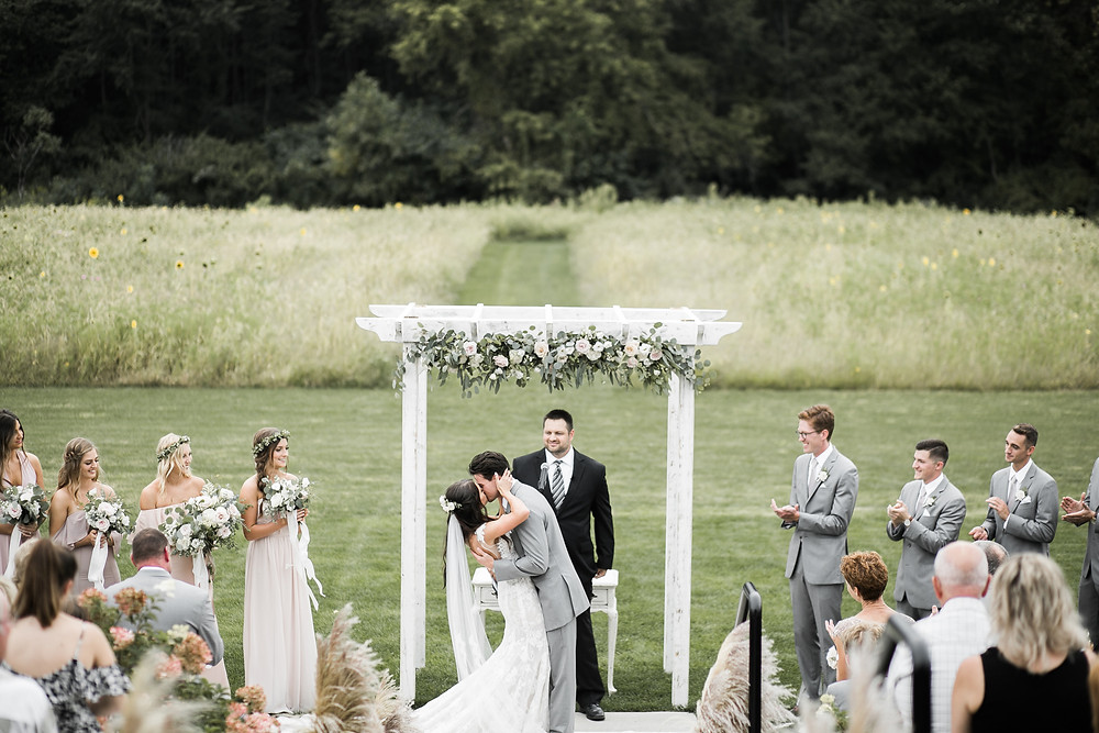 bride and groom kissing under white arbor with flowers after outdoor wedding ceremony at ashton hill farm
