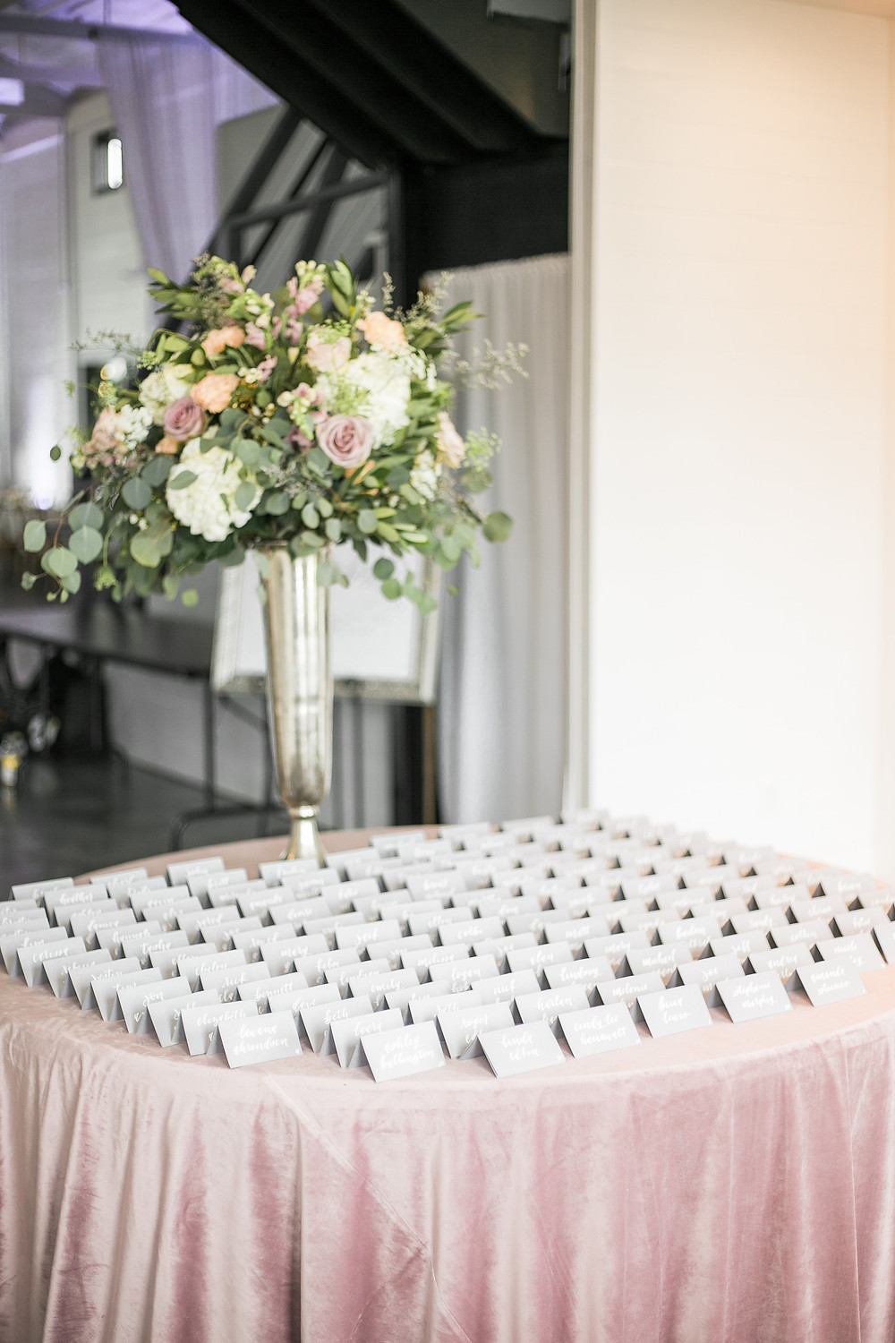 escort card table with grey cards, mauve velvet tablecloth and a tall flower centerpiece in silver vase by studio bloom iowa