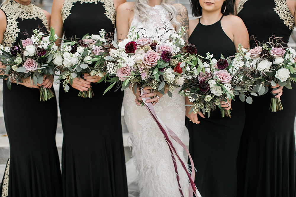 Studio bloom iowa wedding bouquets in mauve, burgundy, and white flowers held by bride and bridesmaids in black and gold dresses