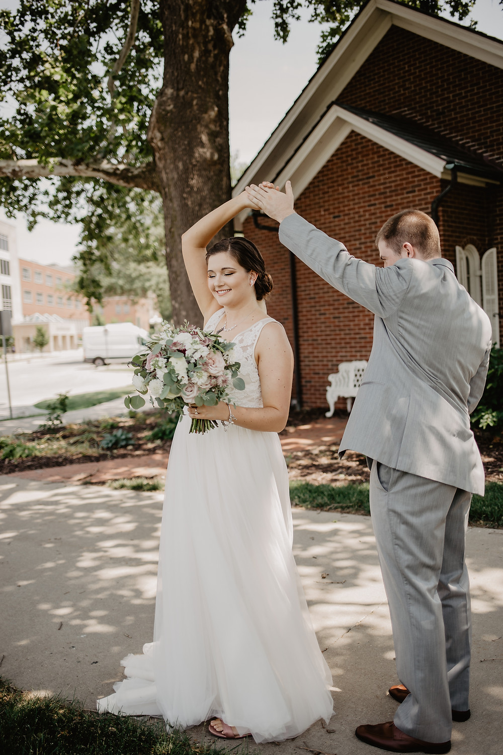 Bride and groom dancing in front of iowa memorial union chapel with bridal bouquet by studio bloom iowa