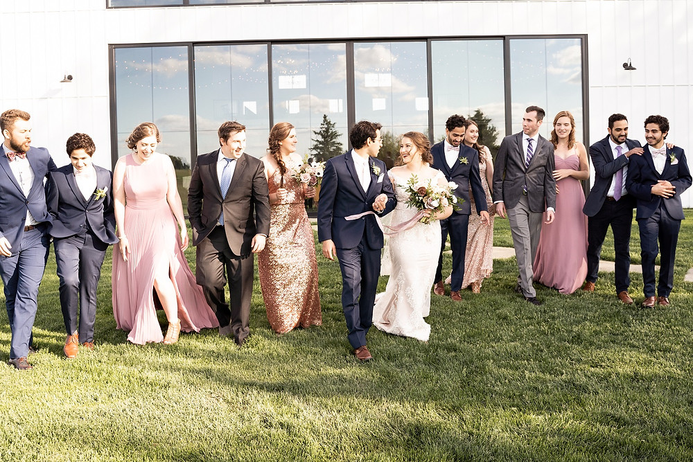 happy bridal party in mauve dresses and navy suits