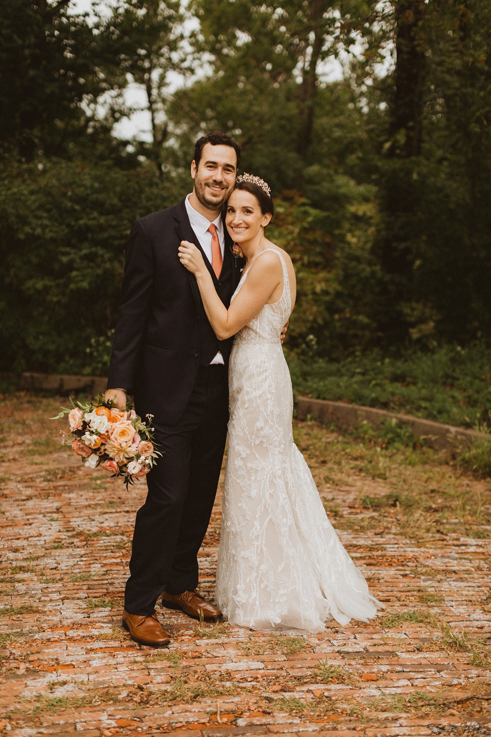 bride and groom with peach garden flower bouquet by Studio Bloom Iowa weddings