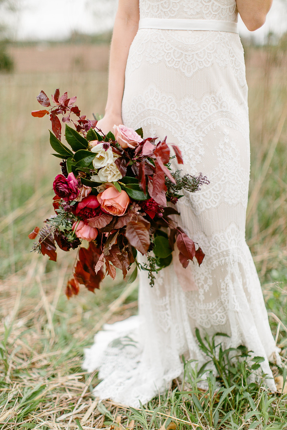 bride holding burgundy wedding flower bouquet by studio bloom iowa in grass prairie