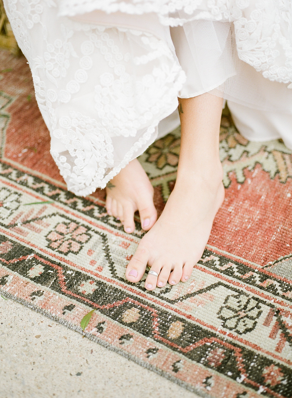 brides feet on a vintage boho rug in shades of rust, cream, and brown