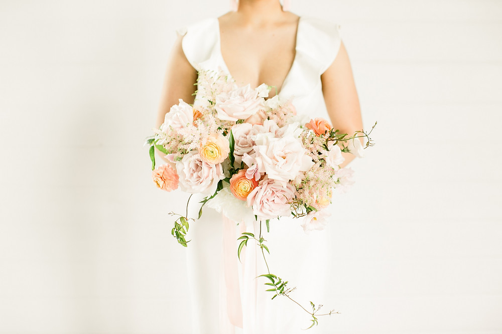 Studio Bloom Iowa bridal bouquet in blush pink and peach with roses, ranunculus, astilbe, and jasmine vine at Ashton Hill Farm