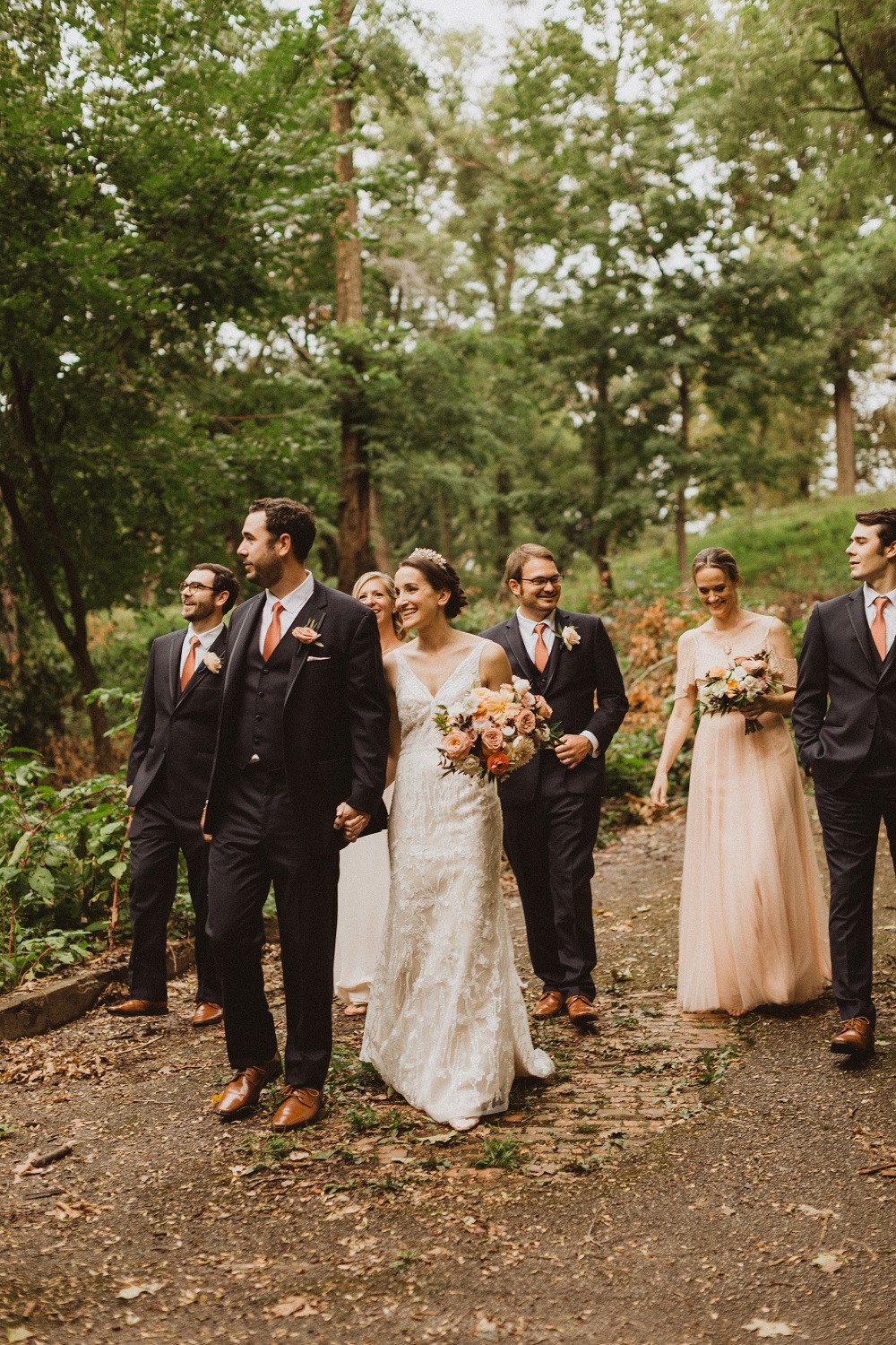 bridal party walking through forest with Studio Bloom Iowa wedding flowers