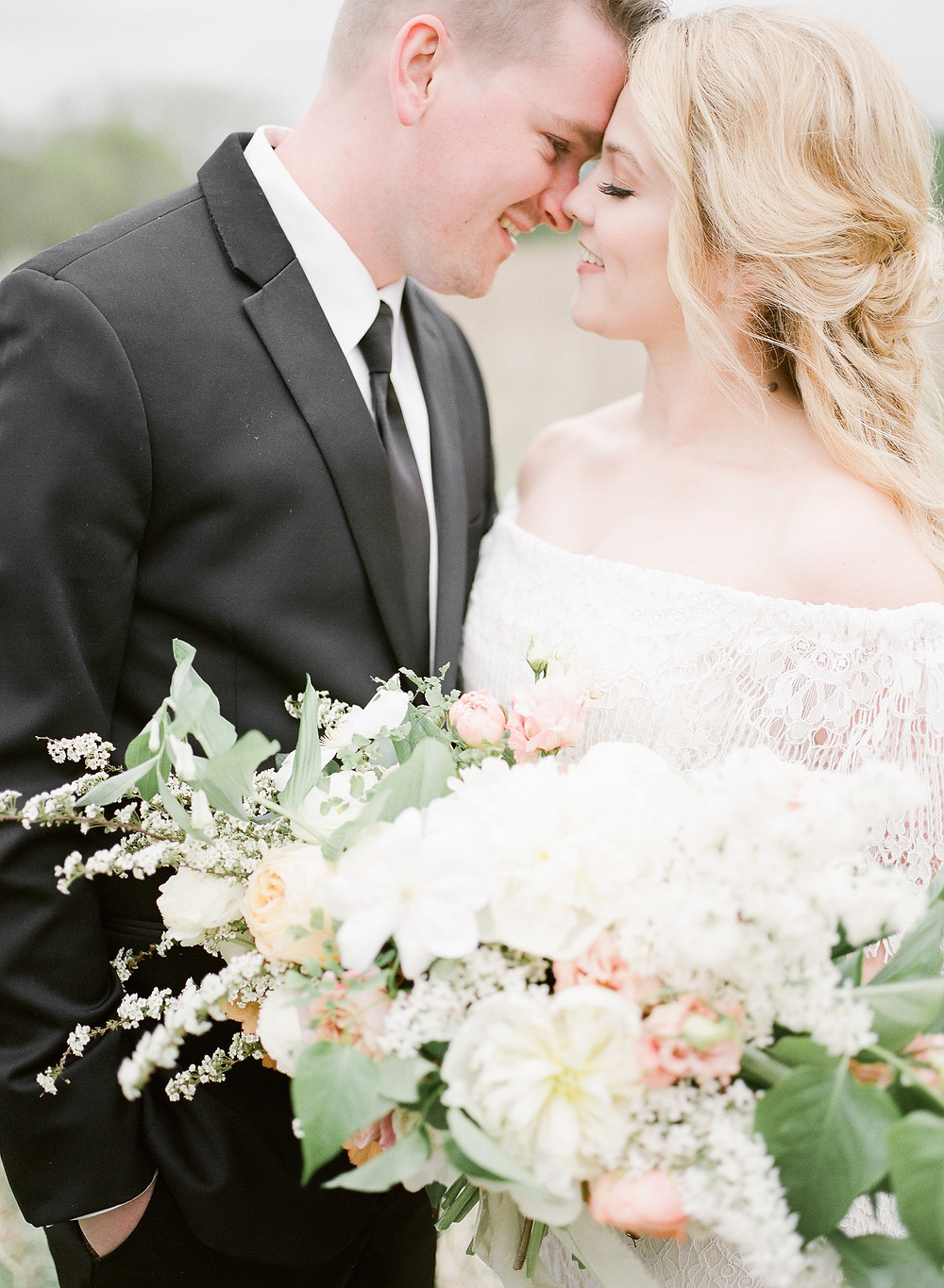 country bride and groom kissing with spring wedding flower bouquet by studio bloom iowa