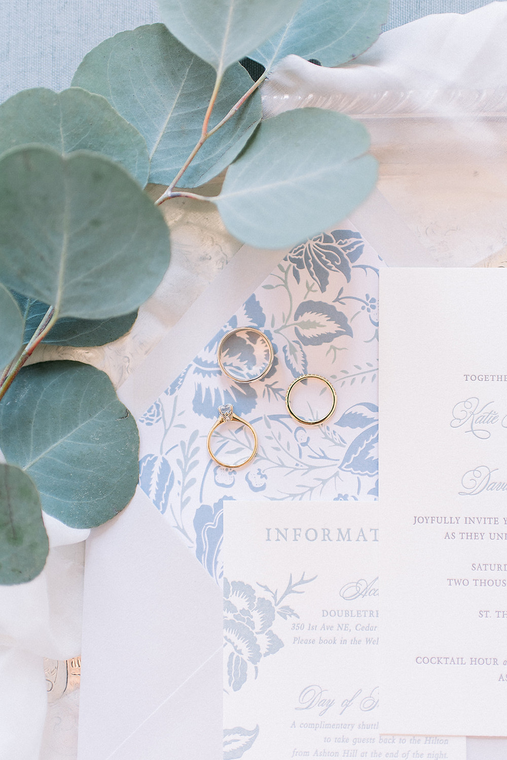 Detail of wedding rings on blue and white invitation with eucalyptus