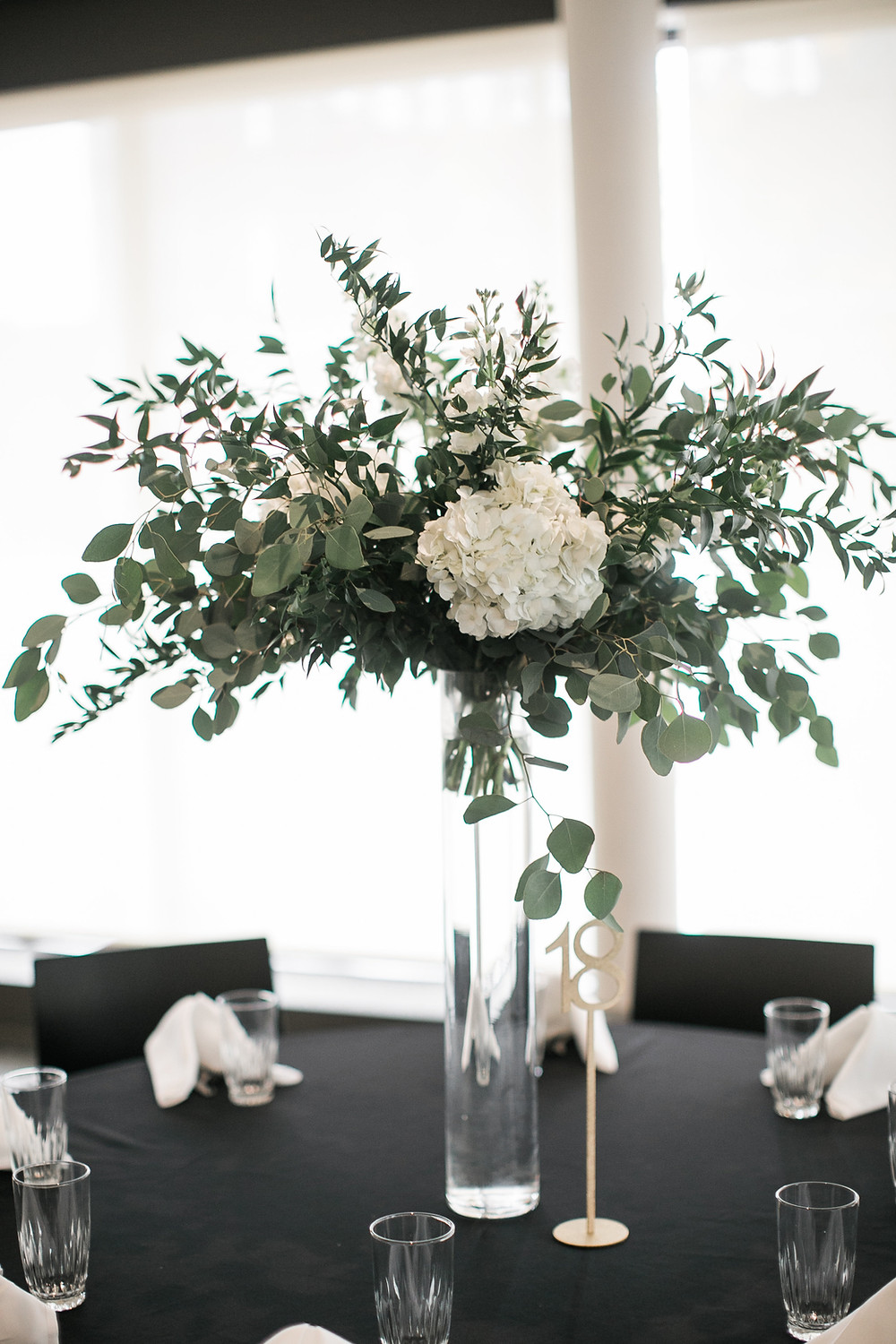 tall centerpiece of eucalyptus and ruscus greenery foliage with white hydrangea in clear vase by studio bloom wedding florist