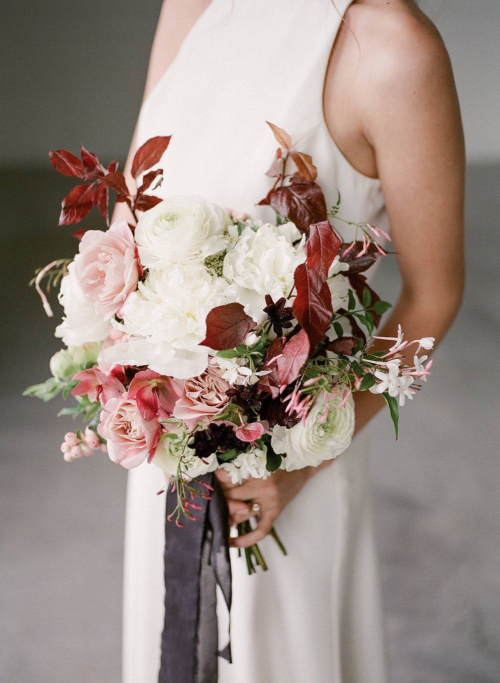 Bridal bouquet by Studio Bloom Iowa of roses, ranunculus, peonies, plum, and flowering branches in mauve and burgundy