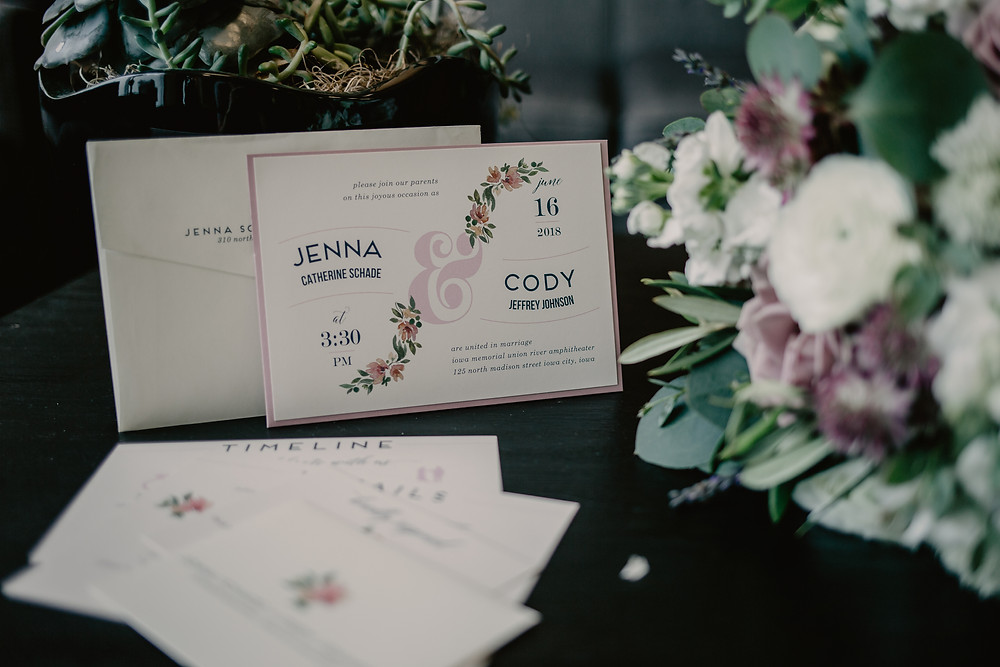 detail photograph of mauve and white floral wedding invitation and bridal bouquet