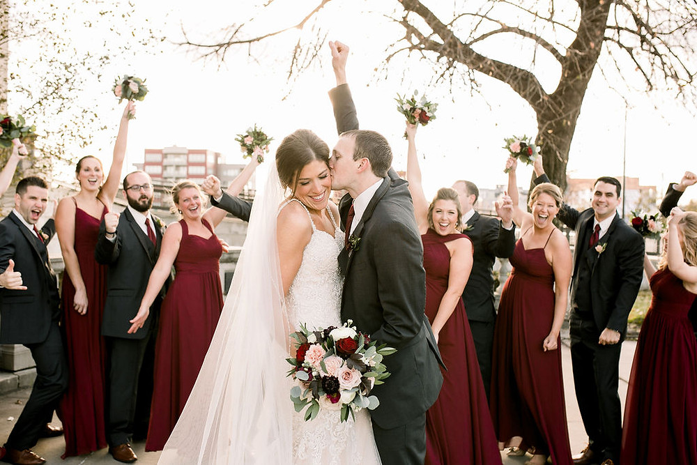 Bridal party cheering in burgundy dresses and black tuxes holding wedding bouquets by Studio Bloom Iowa florist Cedar Rapids