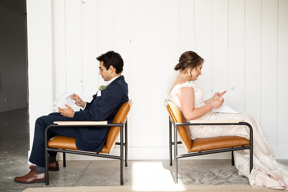 bride and groom sitting in chairs reading love letters
