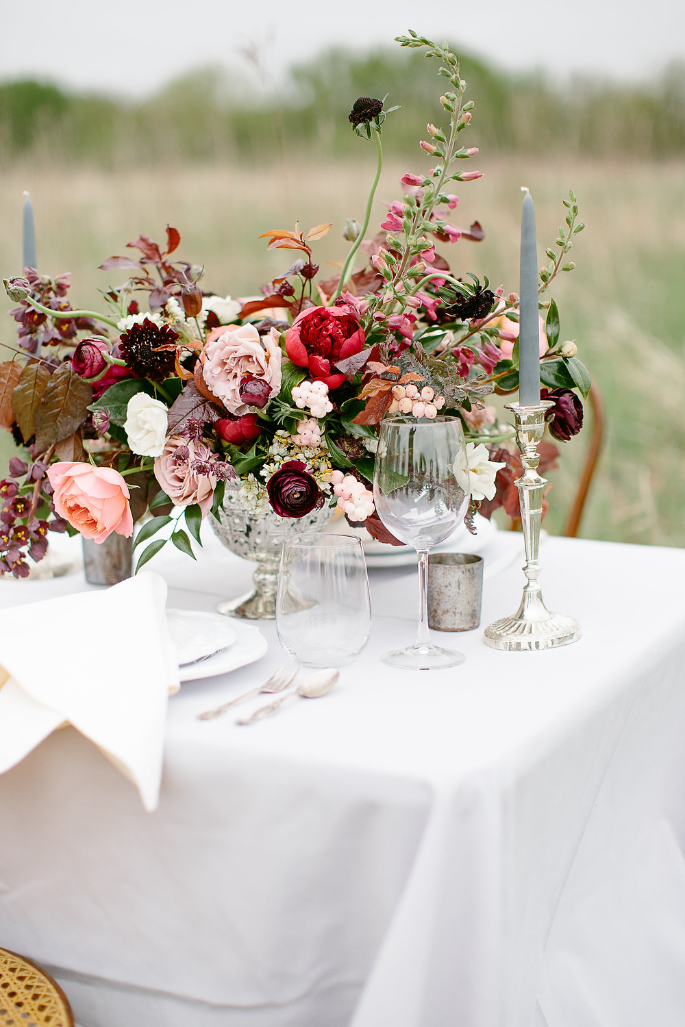 whimsical wedding reception floral centerpiece by studio bloom iowa in tones of burgundy and peach in silver mercury glass