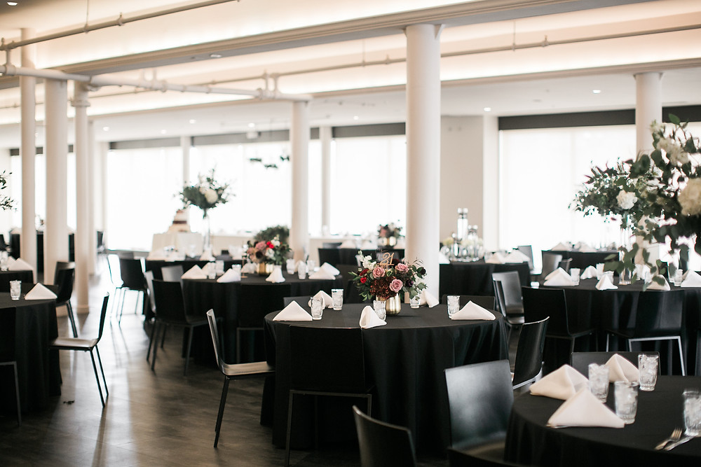 Modern wedding reception at eastbank venue with black tablecloths and flower centerpieces by studio bloom iowa