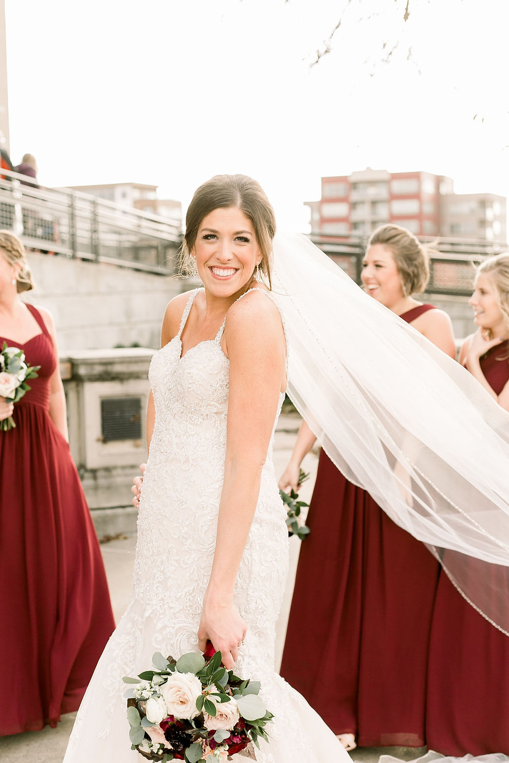 Smiling bride in downtown Cedar Rapids holding burgundy and blush bridal bouquet by Studio Bloom Iowa