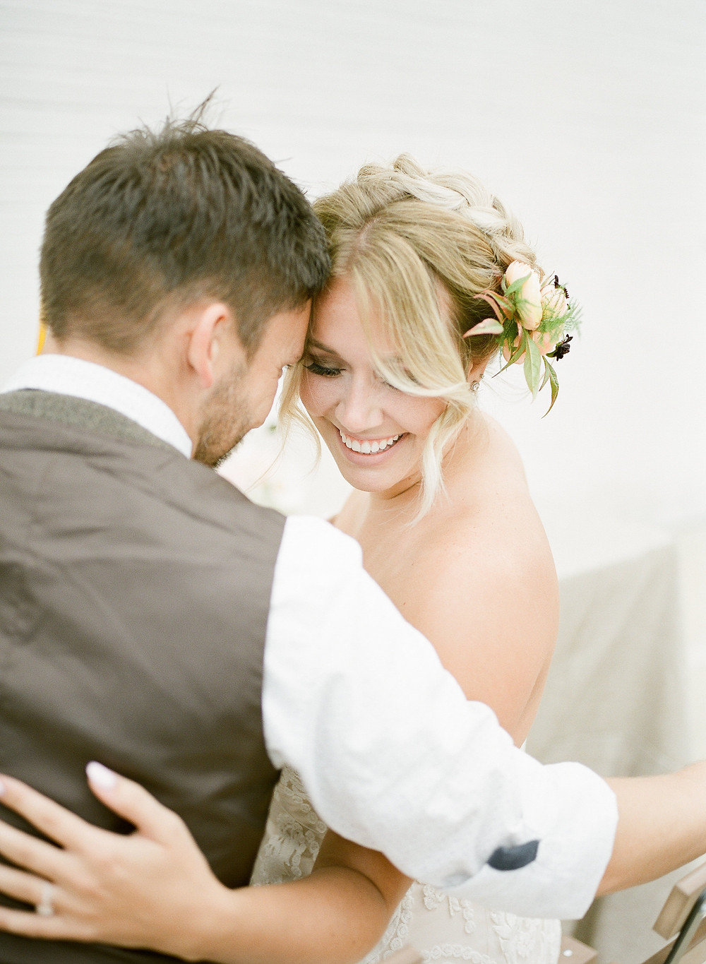 boho bride with flowers in her hair cuddling with groom