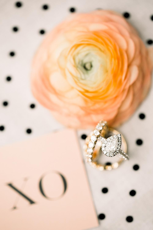 detail of teardrop wedding ring with peach ranunculus on polkadot background