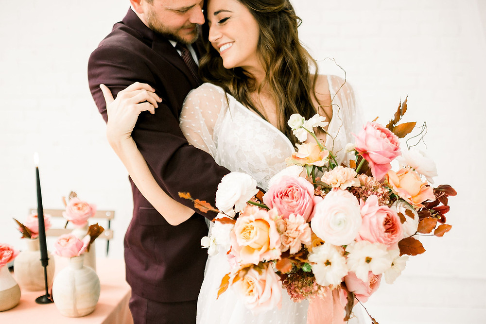 Bride and groom with Studio Bloom Iowa modern bridal bouquet of garden roses, ranunculus, and orchids in pinks and peaches