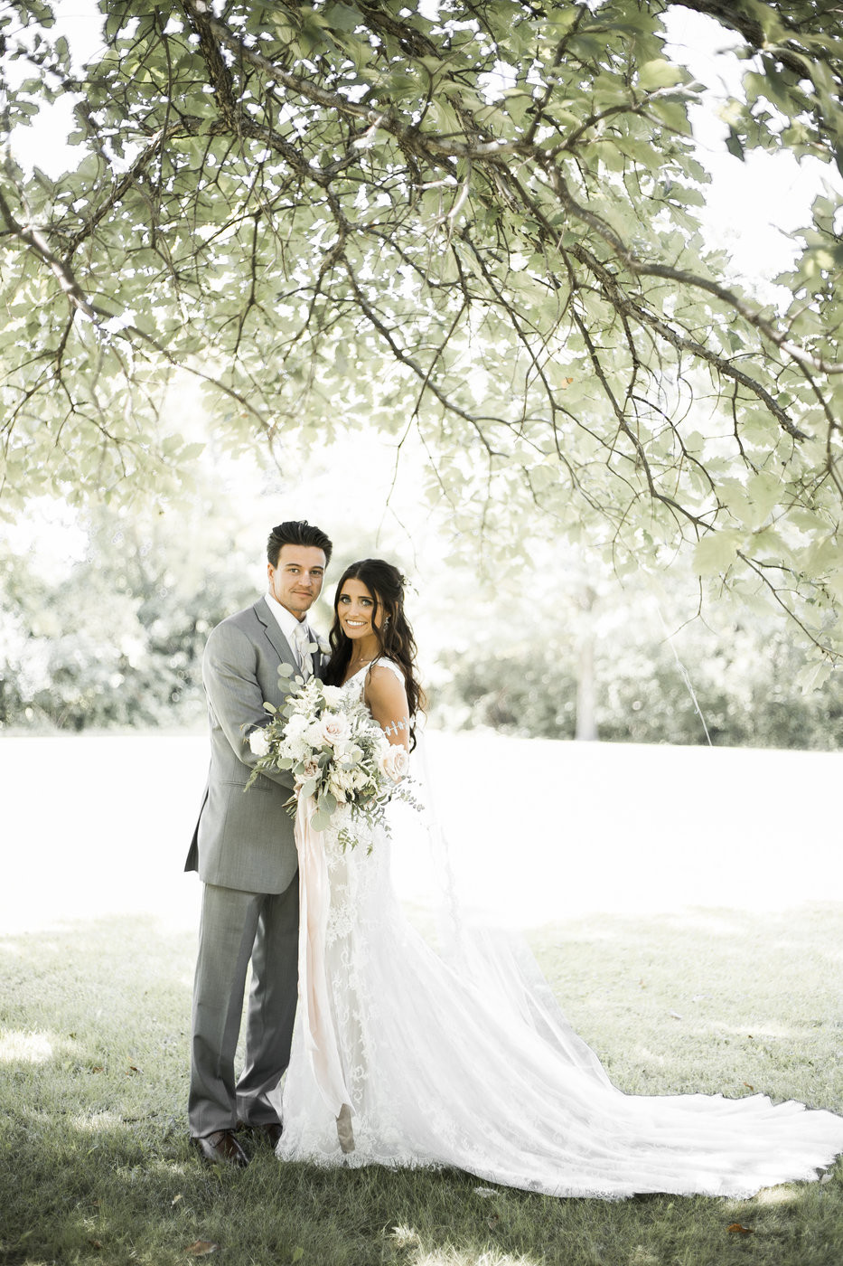 bride and groom posing outdoors under large tree holding garden style wedding bouquet by studio bloom iowa