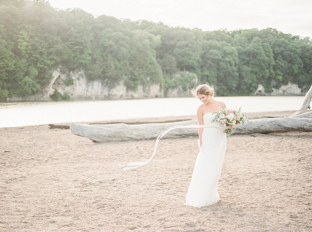 Bride at Palisades Kepler Park beach with holding studio bloom iowa wedding florist bridal bouquet of king protea and roses