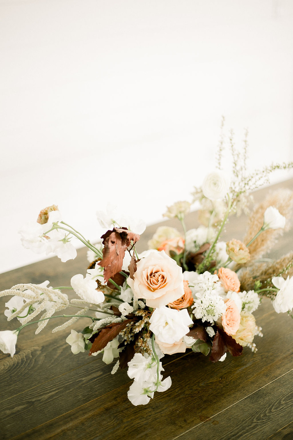 Studio Bloom Iowa minimalist farm centerpiece in neutral peach and brown with roses, scabiosa, sweet pea, and pampas grass