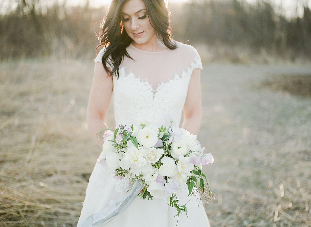 bride in field holding bridal bouquet by studio bloom iowa wedding florist with white peonies and tulips