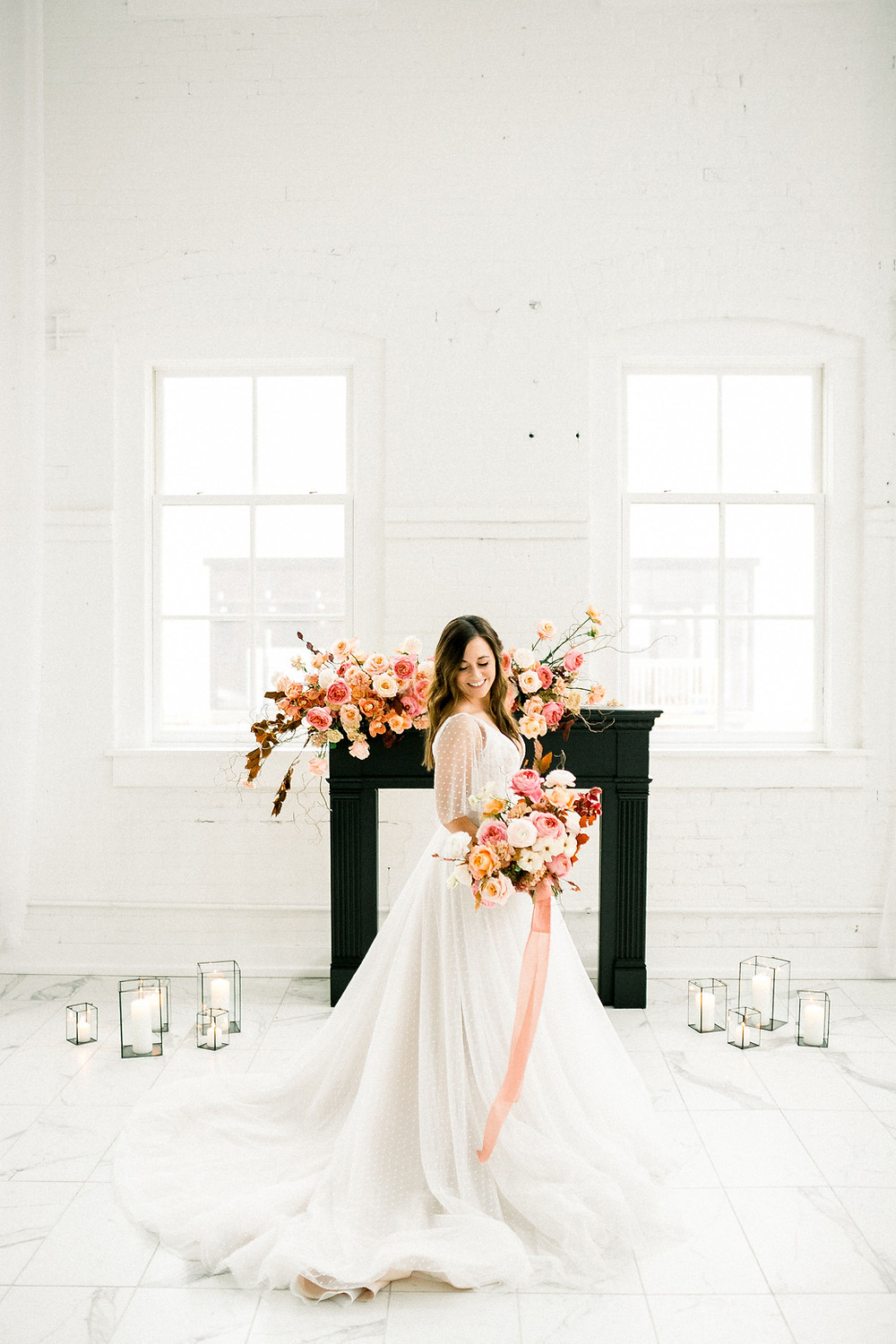 Bride in front of black fireplace mantel with modern pink and peach wedding flowers by Studio Bloom Iowa