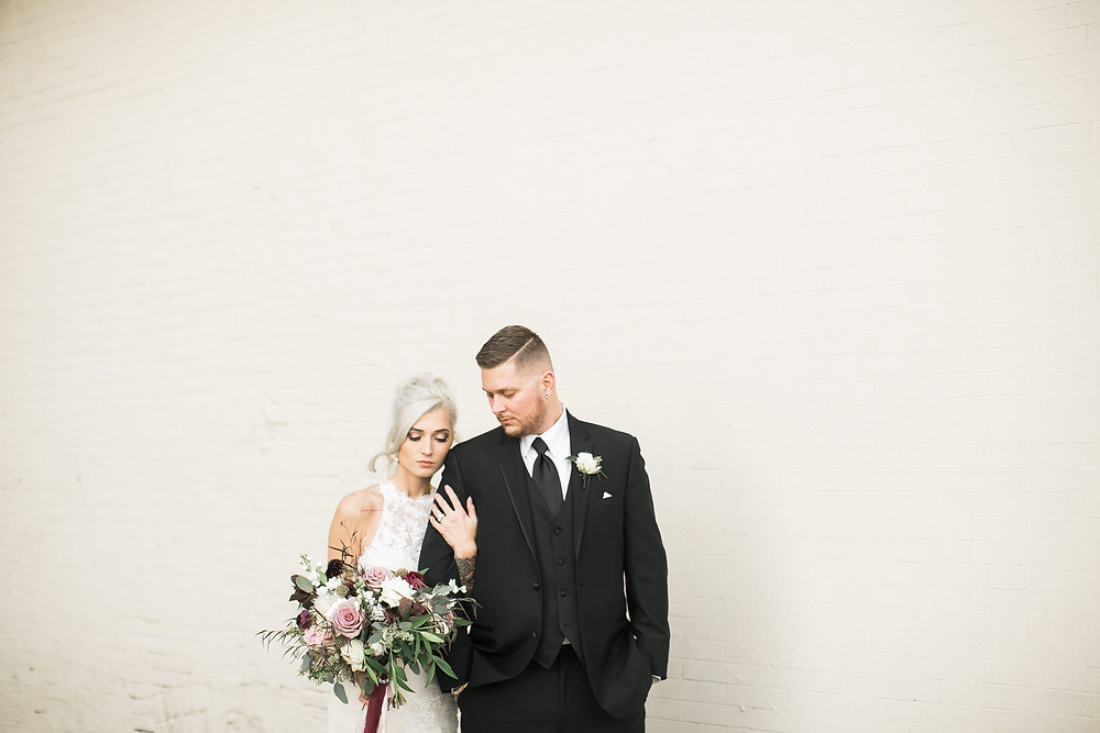 bride and groom posing against white brick wall with bridal flower bouquet by studio bloom iowa for cedar rapids wedding