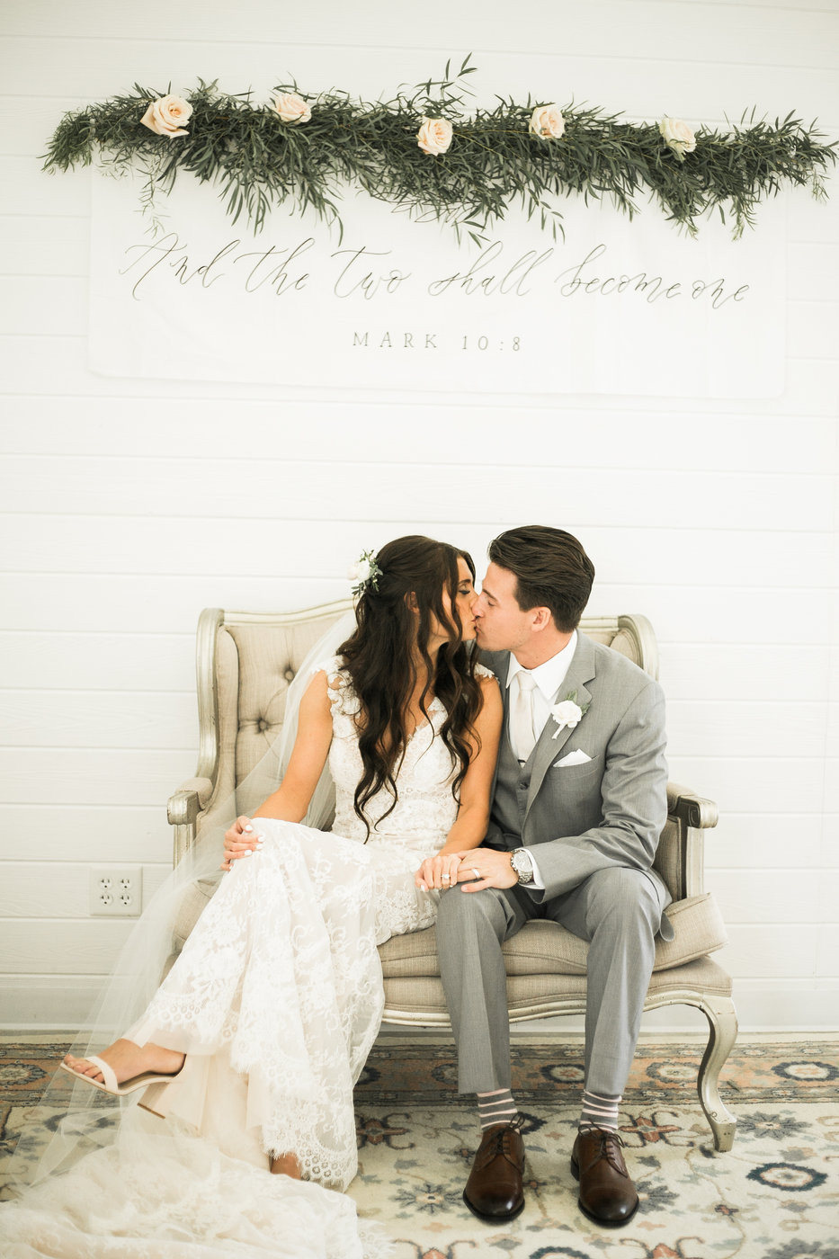 bride and groom kissing on couch with mark 10:8 scripture banner sign and greenery hung on shiplap wall at ashton hill