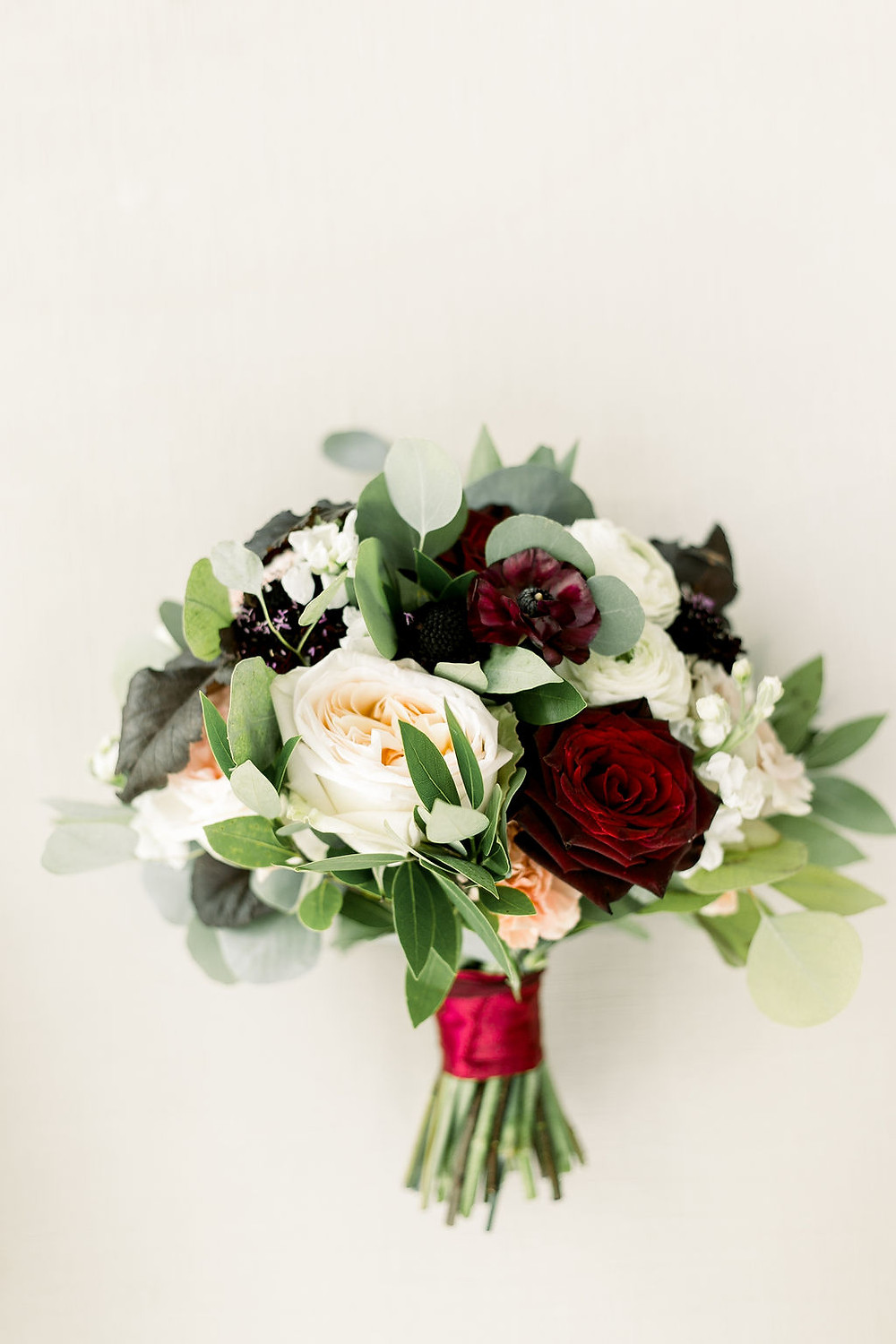 Classic bridal bouquet in burgundy and blush by Studio Bloom Iowa of garden roses, ranunculus, carnations, and eucalyptus