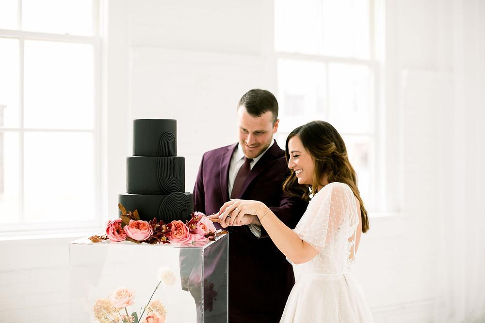 bride and groom cutting modern black fondant wedding cake