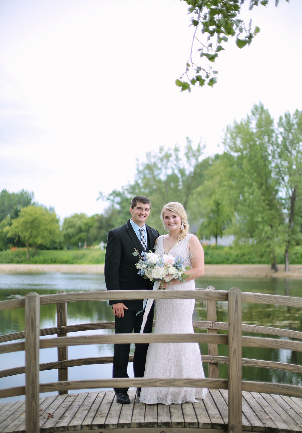 bride and groom at a pond with bridal bouquet by Studio Bloom Iowa wedding florist