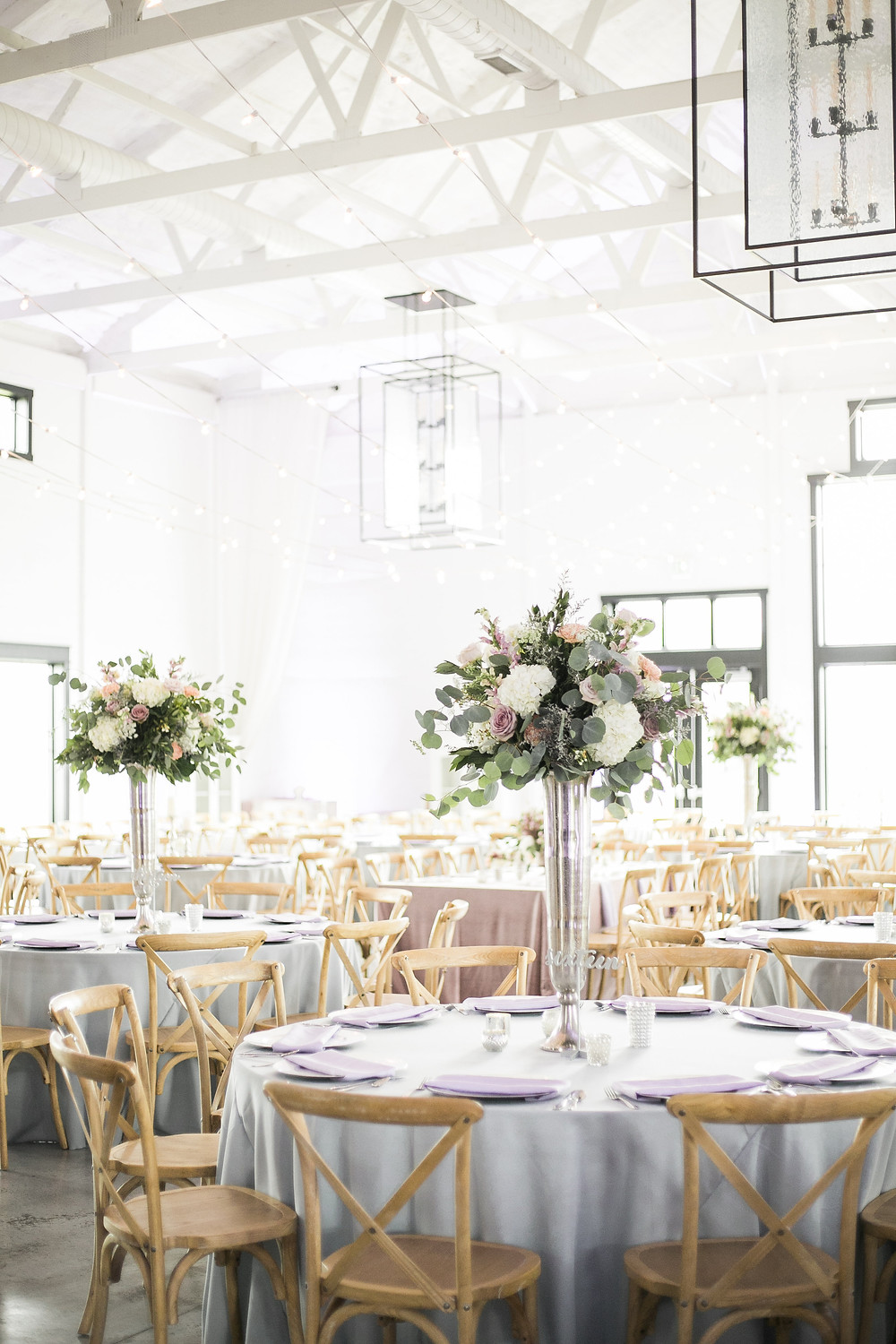 tall flower centerpieces in silver vases by studio bloom iowa with white hydrangea, mauve roses, snapdragons, and eucalyptus