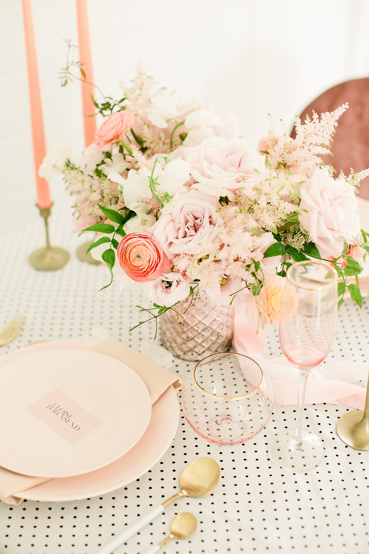 Blush and peach garden centerpiece by Studio Bloom Iowa wedding florist of roses, ranunculus, astilbe, and jasmine vine